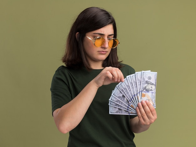Невежественная молодая симпатичная кавказская девушка в солнцезащитных очках держит и смотрит на деньги на оливково-зеленом