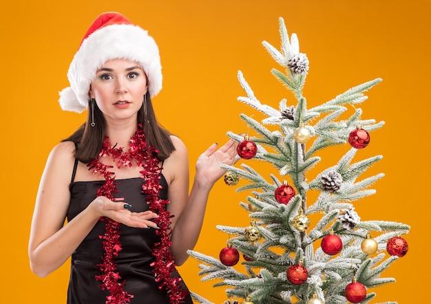 オレンジ色の背景に分離されたカメラを見てそれを指している装飾されたクリスマスツリーの近くに立っている首の周りにサンタの帽子と見掛け倒しの花輪を身に着けている無知な若いかなり白人の女の子