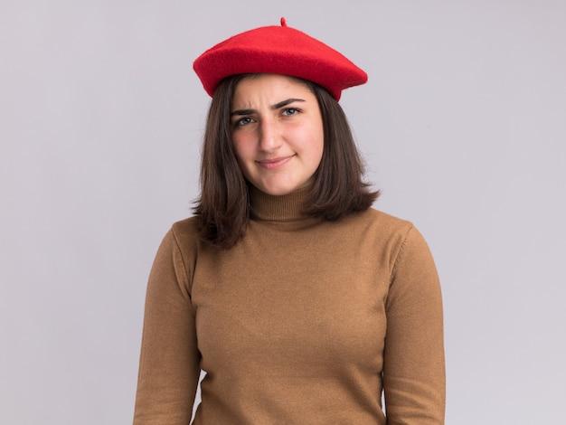 コピースペースと白い壁に分離されたベレー帽の帽子を持つ無知な若いかなり白人の女の子