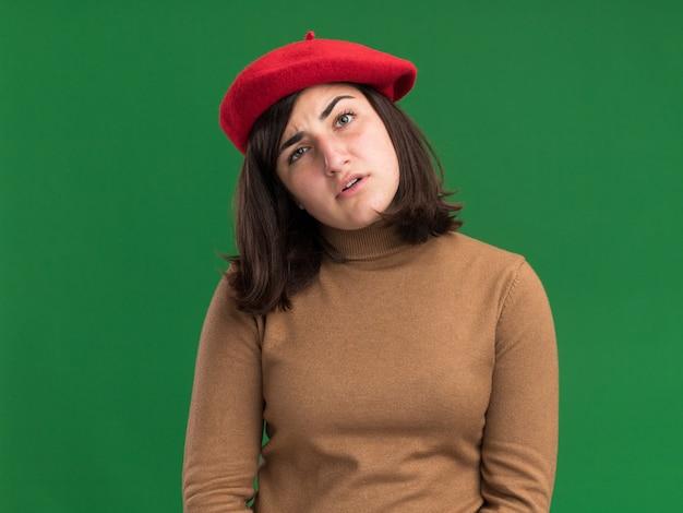 Бестолковая молодая симпатичная кавказская девушка в берете смотрит в камеру, изолированную на зеленой стене с копией пространства