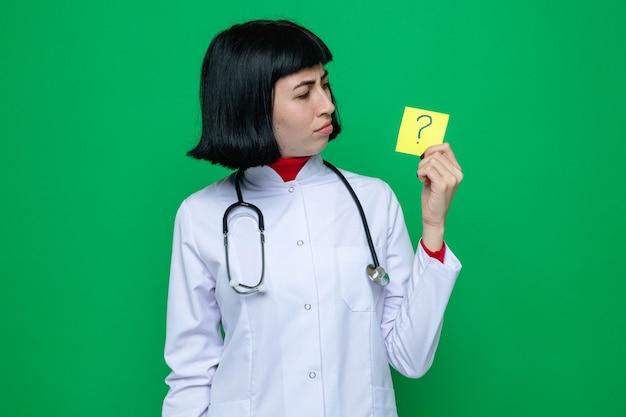 Giovane e bella donna caucasica senza indizi in uniforme da medico con uno stetoscopio che tiene in mano e guarda la nota della domanda
