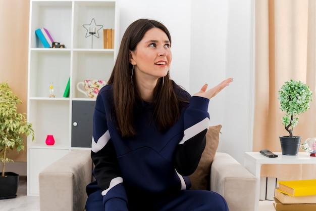 빈 손을 보여주는 디자인 거실에서 안락의 자에 앉아 측면을보고 우 둔 젊은 예쁜 백인 여자