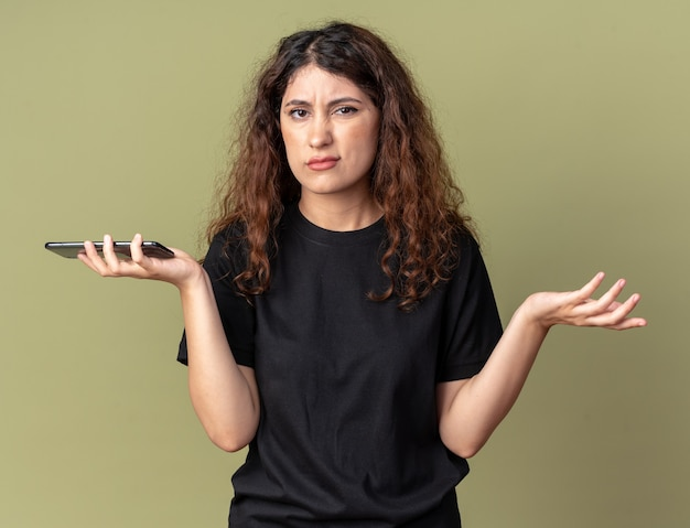 Giovane ragazza graziosa senza indizi che tiene il telefono cellulare che mostra la mano vuota isolata sulla parete verde oliva