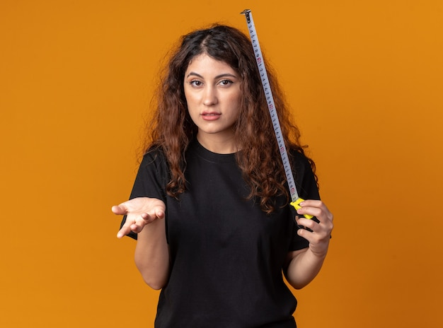 Clueless young pretty girl holding tape meter showing empty hand  isolated on orange wall with copy space