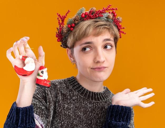 オレンジ色の背景で隔離の空の手を示す側を見てサンタクロースのクリスマスの飾りを保持しているクリスマスの頭の花輪を身に着けている無知な若いかわいい女の子