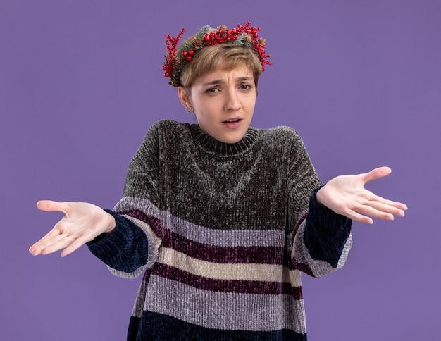 紫色の背景で隔離の空の手を示すカメラを見てクリスマスのヘッドリースを身に着けている無知な若いかわいい女の子