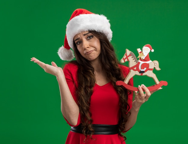 Clueless young pretty girl wearing santa hat holding santa on rocking horse figurine looking at camera showing empty hand isolated on green background