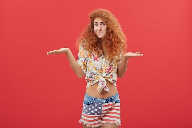 Clueless giovane donna dai capelli rossi che indossa camicia casual e pantaloncini