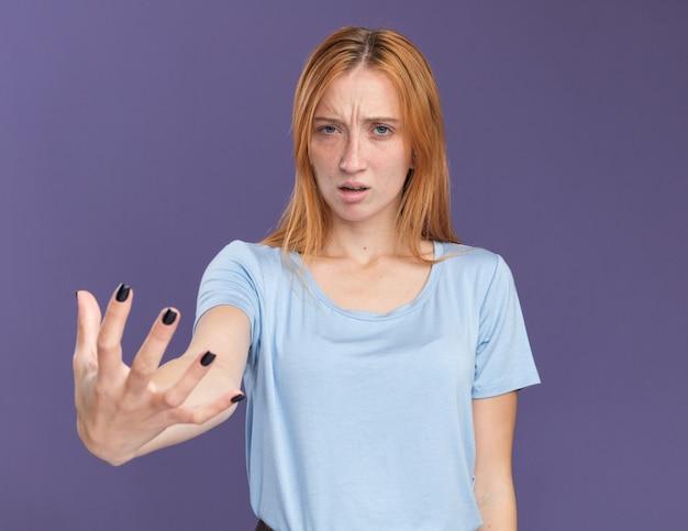 La giovane ragazza rossa dello zenzero senza indizi con le lentiggini tiene la mano aperta isolata sulla parete viola con lo spazio della copia
