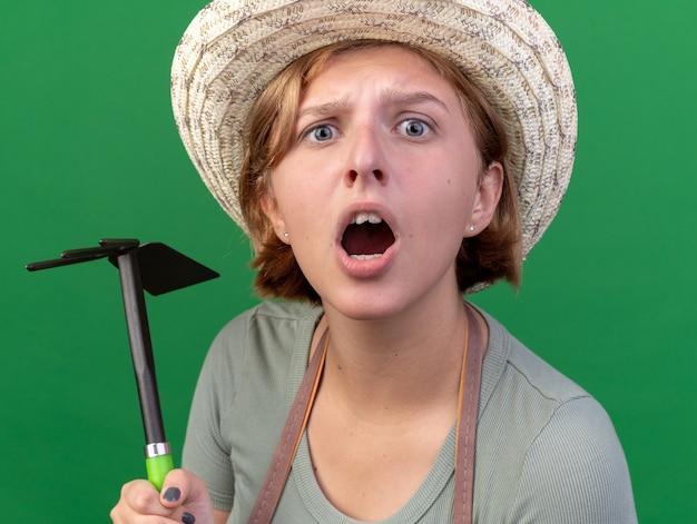 鍬熊手を保持し、カメラを見ている園芸帽子をかぶっている無知な若いスラブ女性の庭師