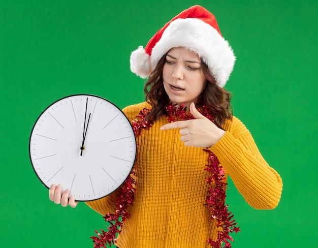 Clueless giovane ragazza slava con santa hat e con una ghirlanda intorno al collo tenendo e indicando l'orologio isolato su sfondo verde con spazio di copia