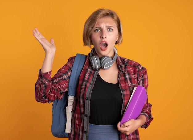 頭を上げた手でバックパック スタンドを着たヘッドフォンを付けた無知な若いスラブ学生の女の子が本とノートを保持している