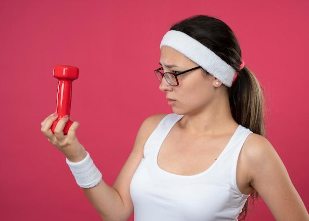 Невежественная молодая спортивная девушка в оптических очках с повязкой на голову и браслетами держит и смотрит на гантели