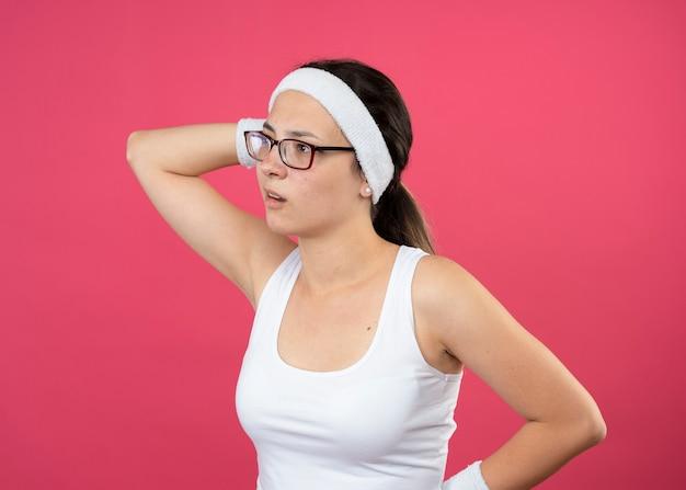 La giovane donna sportiva senza tracce in vetri ottici che indossa la fascia e i braccialetti tiene la testa e guarda al lato isolato sulla parete rosa