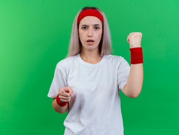 머리띠와 팔찌를 착용하는 중괄호가있는 우 둔 젊은 스포티 한 여자는 녹색 벽에 고립 된 앞에서 주먹과 포인트를 유지합니다.