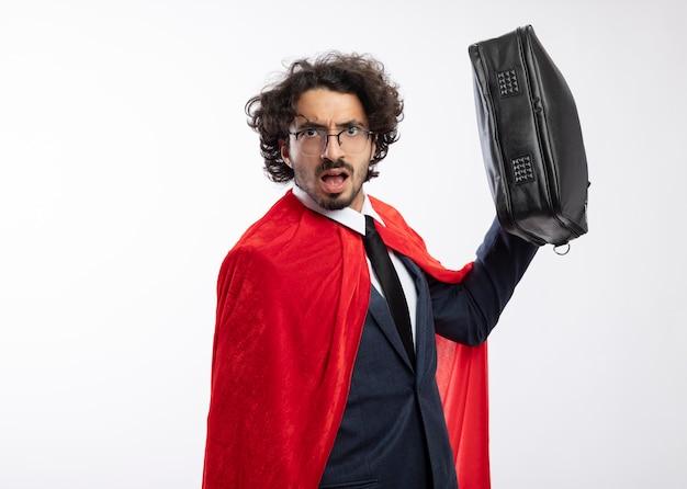 赤いマントとスーツを着て光学メガネの無知な若いスーパーヒーローの男は、白い壁に分離された革のハンドバッグを保持します
