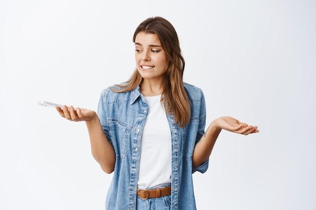 Бестолковая молодая женщина со светлыми волосами и татуировками, пожимая плечами, озадаченно глядя на смартфон, стоит у белой стены