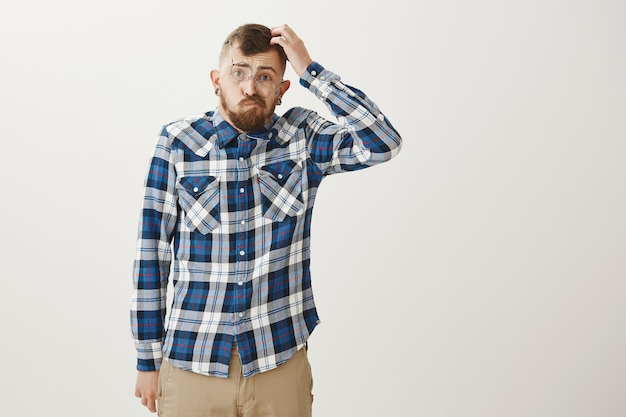 Clumsy bearded young man in crooked glasses looking indecisive and puzzled, scratch head