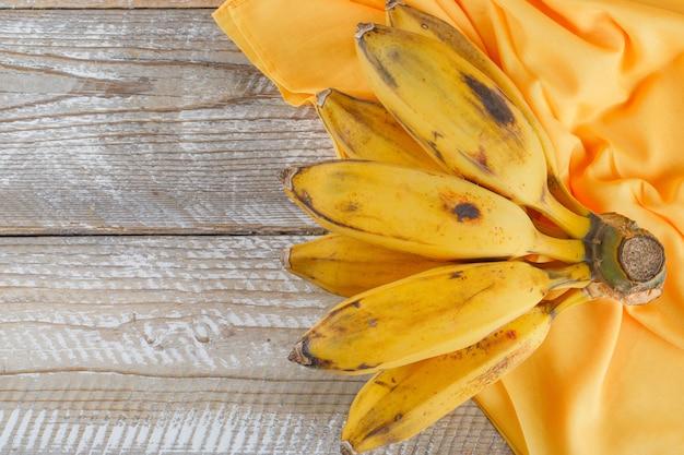 Grappolo di banane piatto giaceva su legno e tessuto