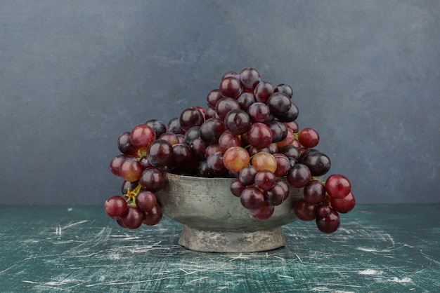 A cluster of black grapes in the vase on marble table.