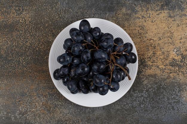 Grappolo d'uva nera sulla zolla bianca.