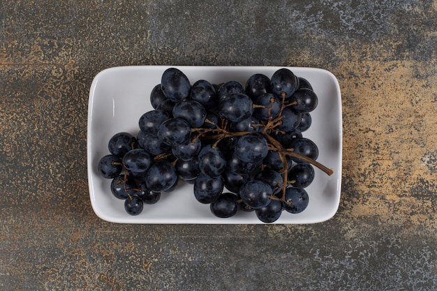 Cluster of black grapes on white plate.