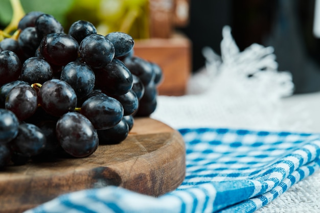 A cluster of black grapes on wooden plate with blue tablecloth