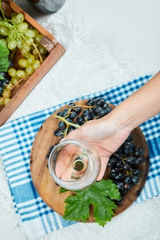 A cluster of black grapes on wooden plate with leaf while hand holding an empty glass