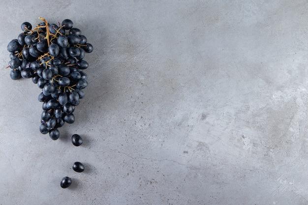 Grappolo di uva nera fresca posto su sfondo di pietra.