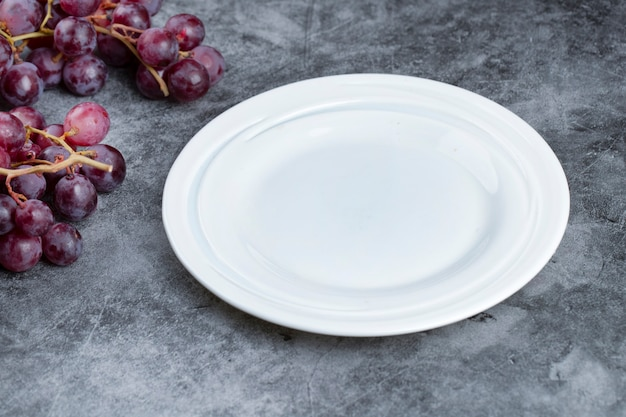 Cluster of fresh red grapes and empty plate on marble background.