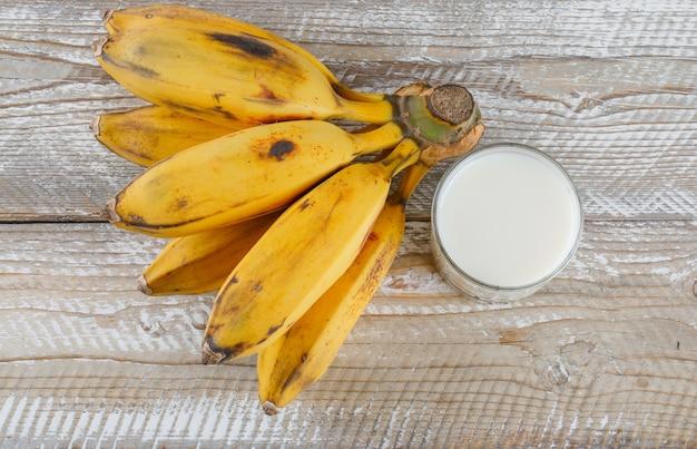 Гроздь бананов с молоком плоская лежала на деревянном