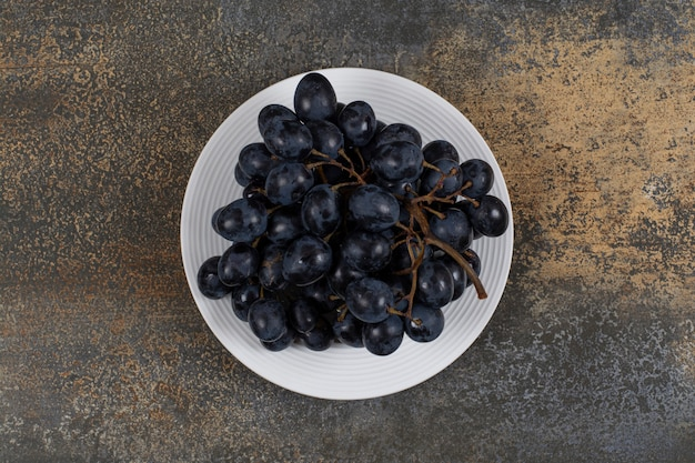 Гроздь черного винограда на белой тарелке.