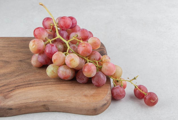 Гроздь свежего винограда на деревянной доске.