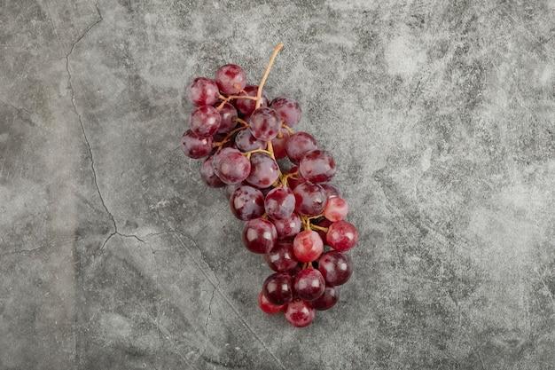 大理石の表面に赤く新鮮な熟したブドウの房。