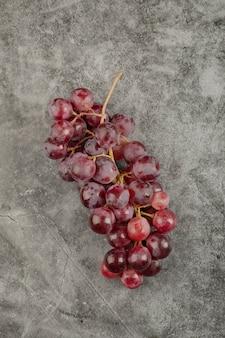大理石の表面にある赤くて新鮮な熟したブドウの房。