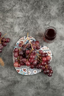 Cluster of red fresh grapes and glass of juice on marble table.
