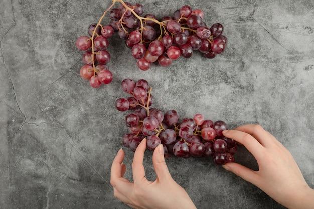 Grappolo di uva matura fresca rossa sulla superficie di marmo.