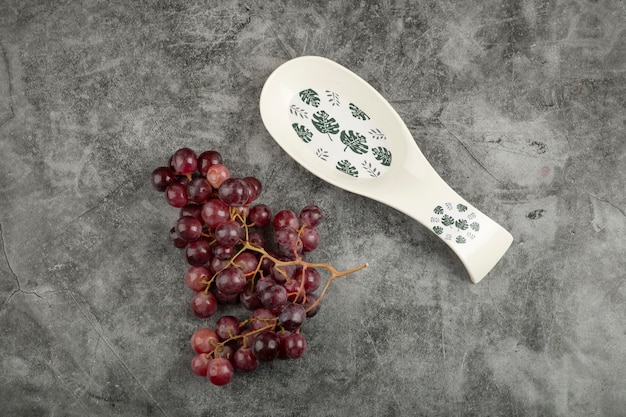 Cluster of red grapes and empty white plate on marble surface.