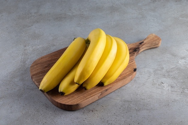 Cluster of ripe bananas placed on wooden cutting board