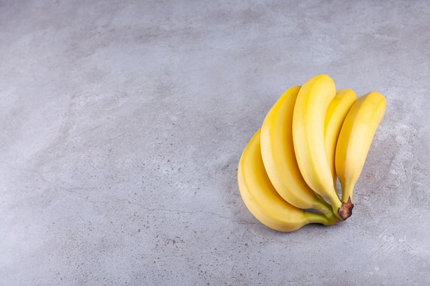 Cluster of ripe yellow bananas placed on stone background.
