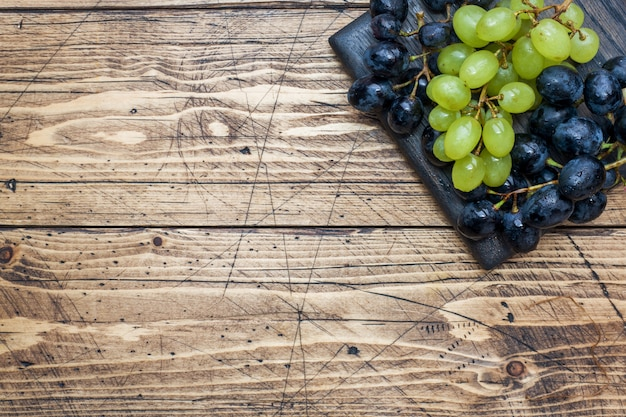 Clusters of black and green grapes kish mish on a wooden board. copyspace.