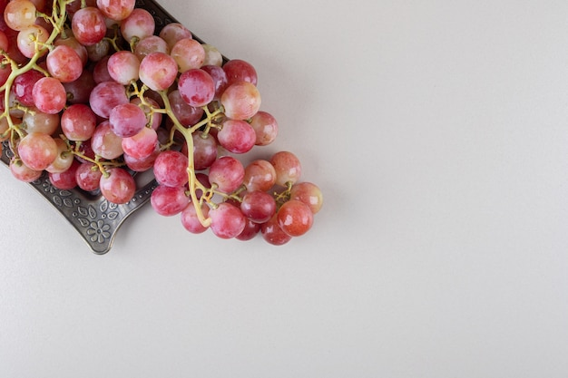 Clusters of grape and an ornate tray on marble