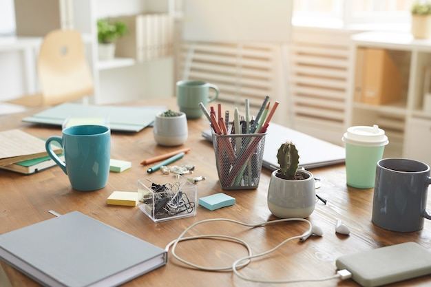 Cluttered workplace table with cups, mugs and stationary items, teamworking or studying concept