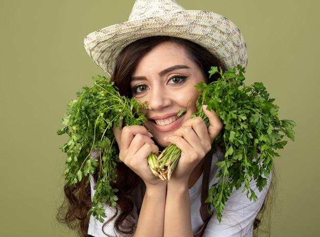 Улыбающаяся молодая женщина-садовник в униформе в садовой шляпе держит кориандр на оливково-зеленом