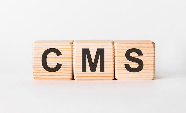 Буквы cms деревянных блоков в форме колонны на белом, копией пространства