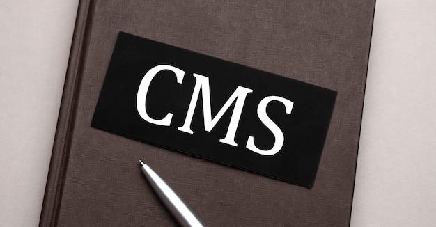 갈색 메모장의 검은 색 스티커에 쓰여진 cms 기호. 세금 개념