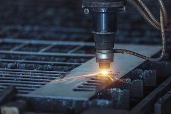 CNC Laser cutting of metal, modern industrial technology. Small depth of field.