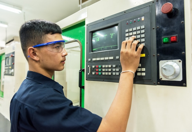 Cnc operator, mechanical technician worker at metal machining milling center in tool workshop