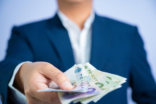 中国のお金は青いスーツcnyを着てビジネスマンを手に保持します。