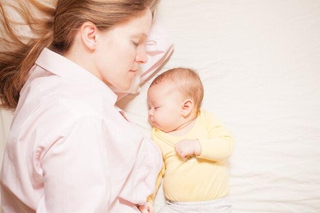 침대에서 모유 수유 후 함께 자는 엄마와 3개월 아기